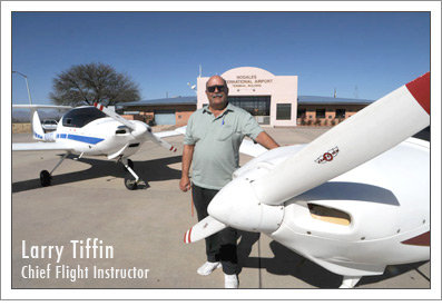 Chief Flight Instructor Larry Tiffin stands between 2 propeller planes.