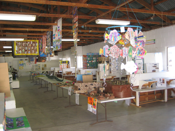 Photo looking down along the tables covered in art.