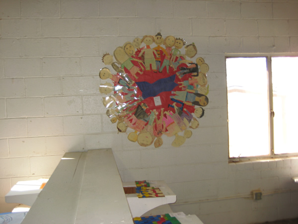 Paper children stand in a circle on poster board.