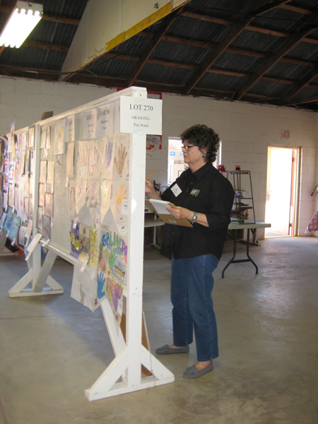 A judge inspects the student art.