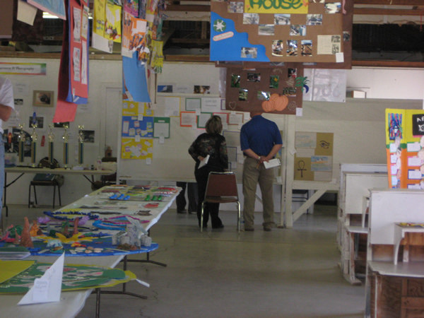 Two judges inspect some art.