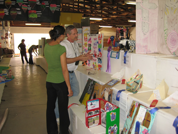 Two people closely examine the art in the exhibit.