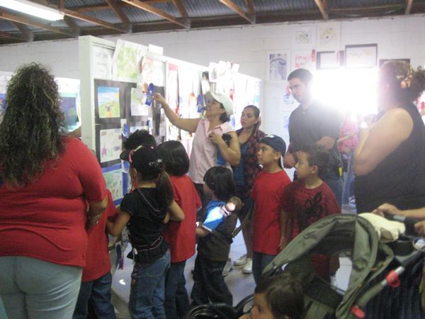 A large group gathers around some student art.