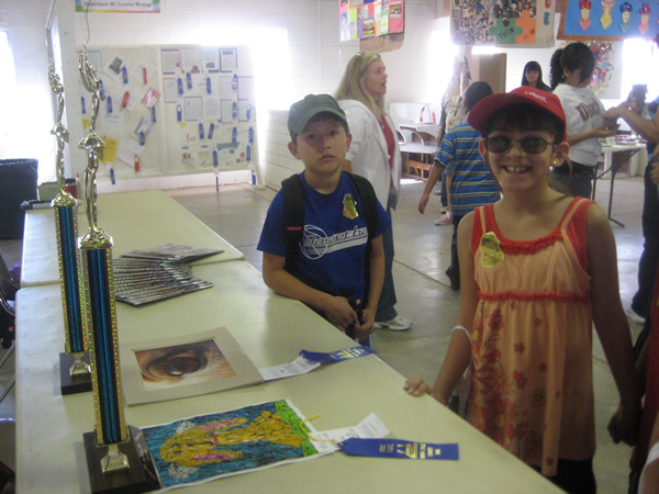Two kids smile for the camera at the trophy table.
