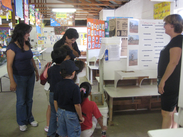 People stand around a display, listening to a student's presentation.